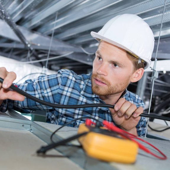 Electrician Running Wires In Suspended Ceiling